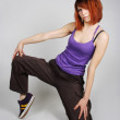 Young redhead girl in hip-hop clothes sitting on one knee and lo — Stock Photo