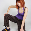 Young redhead girl in hip-hop clothes sitting on one knee, smili — Stock Photo