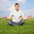 Young handsome man sitting on green summer lawn and meditating  with closed eyes - Stock Photo