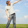 Royalty-Free Stock Photo: Young handsome man standing on summer lawn and pointing for fing