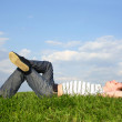 Young handsome man lying on summer lawn with closed eyes, side v — Stock Photo