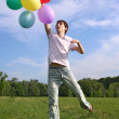 Young man with many colored balloons jumping at green summer law — Stock Photo