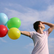 Stock Photo: Young mwith many colored balloons outdoor