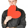 Young caucasian man bite red paper heart isolated — Stock Photo