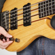 Man tuning bass guitar closeup — Stock Photo