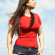 Stock Photo: Young brunette woman in red shirt looking at side, sky with clou