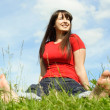 Stock Photo: Young barefooted women siting on summer meadow and smiling, blad