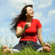 Stock Photo: Young barefooted women siting on summer meadow and smiling, blue