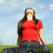 Young girl siting on summer meadow and looking up, blue sky — Stock Photo