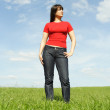 Young girl in red shirt standing on summer meadow, blue sky — Stock Photo
