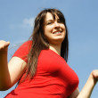 Young girl in red shirt making gesture, blue sky — Stok fotoğraf
