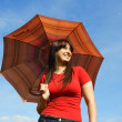 Young brunette girl in red shirt holding red umbrella and smilin — Stock Photo