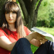 Young brunette girl in red shirt siting near tree and reading bo — Stock Photo