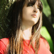 Young brunette girl in red shirt siting near tree and looking at — Stock Photo