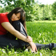 Young brunette girl in red shirt siting near tree and thinking, — Stock Photo