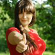 Young brunette girl in red shirt making thumbs up gesture, summe — Stock Photo