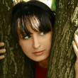 Stock Photo: Young beautiful brunette girl looking out of trees, summer time