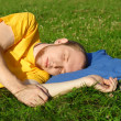 Man in yellow shirt sleeping in summer meadow near clock, lying — Stock Photo