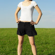 Smiling young girl in skirt standing on summer meadow and hand o — Stock fotografie
