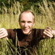 Young man sitting on field in tall grass, smiling and pulling gr — Stock Photo