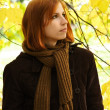Young redhead girl in warm clothes looking at side, autumn tree — Stock Photo