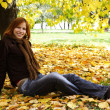 Young redhead girl in warm clothes sitting near autumn tree, smi — Stock Photo
