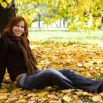 Молодая рыжая девушка в теплой одежде, сидя возле осенних деревьев, smi — Стоковое фото