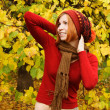 Young redhead girl in warm autumn dress standing outdoor, lookin — Stock Photo #13722276