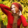 Young redhead girl in warm autumn dress standing outdoor, lookin - Stock Photo
