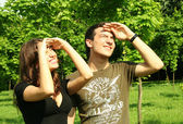 Young man and girl looking at sun — Stock Photo