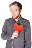 Young man with beard in grey shirt holding red paper heart on hi — Stock Photo