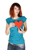 Young redhead girl holding red paper heart on her breast, lookin — Stock Photo