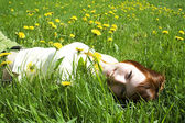 Young redhead girl in yellow shirt lying on grass and smiling — Stock Photo