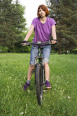 Girl in purple shirt on bicycle in park — Stock Photo