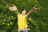 Young girl in yellow shirt lying on grass, smiling and stretchin — Stock Photo