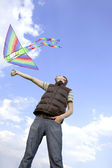 Young man playing with multicolored kite and looking on it, view — ストック写真