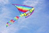 Jasne wielobarwny latawca w błękitne niebo pochmurne — Zdjęcie stockowe