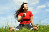 Young barefooted women siting on summer meadow and smiling, blue — Stock Photo