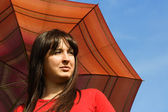 Young brunette girl holding red umbrella, blue sky — Stock Photo