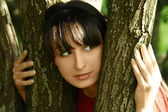 Young beautiful brunette girl looking out of trees, summer time — Stock Photo