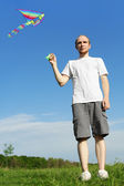 Man in white shirt standing on summer meadow and flying kite, fu — Stock Photo