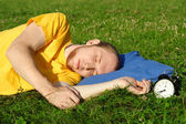 Homme en chemise jaune, dormant dans la prairie d'été près de horloge, couché — Photo