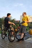 две молодые люди в спортивной одежде, стоя на мосту возле велосипеды — Стоковое фото