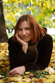 Young redhead girl in warm clothes lying near autumn tree and sm — Stock Photo