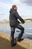 Young man standing on river embankment and looking into the dist — Stock Photo