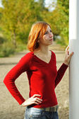 Young redhead girl outdoor, hand on pole, looking at side — Stock Photo