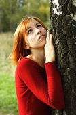 Beauty girl in red dress snuggle up to tree, half body, looking — Stock Photo