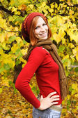 Young redhead girl in warm autumn dress standing and smiling out — Stock Photo