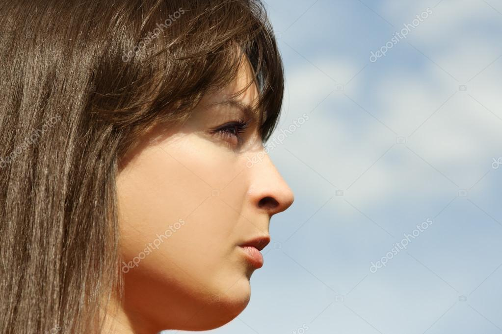 Young brunette girl looking into the distance, blue sky, profile — Stock Photo #13722048