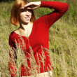 Young girl in red shirt standing on field in tall grass, looking — Stock Photo